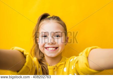 Happiness, Emotions And Fun Concept. Attractive Child Girl In Yellow Sweater, Stretching Hands Towar