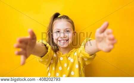 Attractive Child Girl In Yellow Sweater, Stretching Hands Towards Camera To Cuddle, Hold Someone Tig