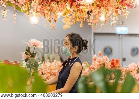 Woman In Medicail Mask Chooses Artificial Flowers In Flower Shop.