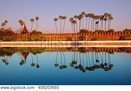Ancient brown brick Palace wall with reflection in the canal surrounding the Mandalay palace located in Mandalay, Burma (Myanmar) at sunrise