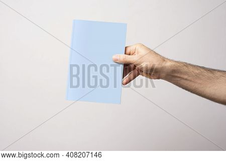 Male Hand Holding A Closed Book-catalog With Blank Cover, Mock-up Series Template Ready For Your Des