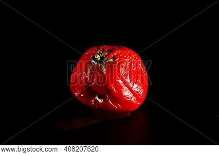 Bright Spoiled Tomato Isolated On A Black Background, Close-up. Violation Of Food Storage Conditions