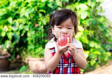 Selective Focus, Hands Have Black Nail Of Child Girl Holding Apple For Eating Healthy. Natural Green