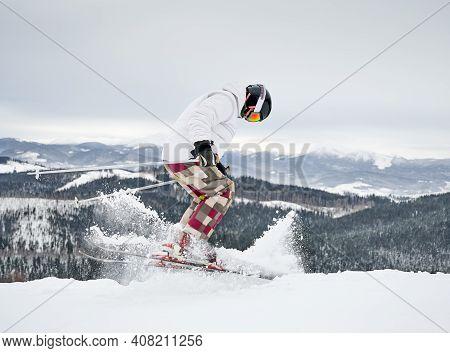 Full Length Of Alpine Skier Skiing On Fresh Powder Snow In Winter Mountains. Man Freerider In Winter