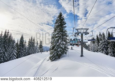 Panorama Of Snowy Hills With Coniferous Trees, Ski Lifts And People Under Blue Cloudy Sky. Scenery O