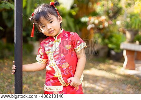 Baby Girl In Red Chinese Outfit Playing In Garden