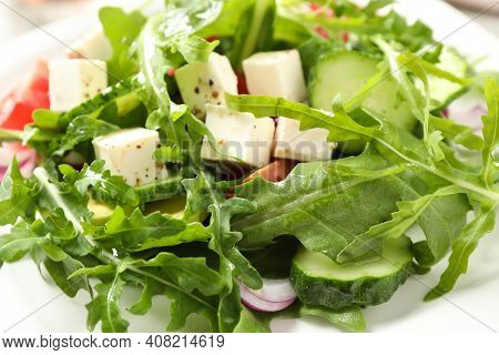 Delicious Salad With Feta Cheese, Arugula And Vegetables On Plate, Closeup
