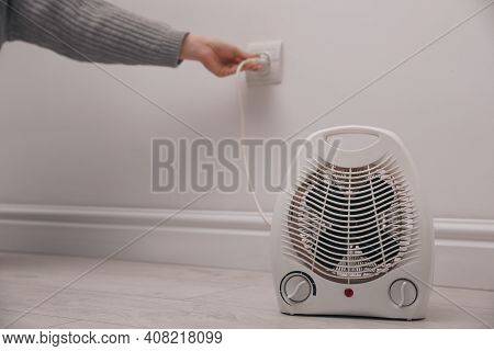 Woman Plug In Modern Electric Fan Heater Indoors, Focus On Device. Space For Text