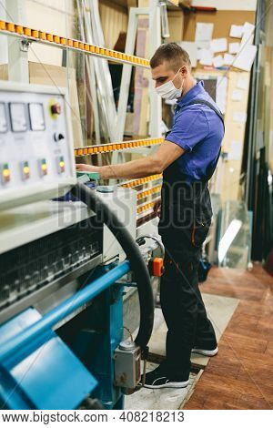 Glazier worker in face mask operates glass cutting machine in workshop. Industry during coronavirus Covid-19