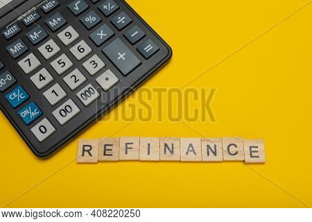 Phrase Or Word - Refinance. Wooden Block Letter Word And Modern Calculator On A Yellow Background, B