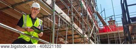 Panorama male builder foreman, construction worker, contractor or architect on building site writing on black clipboard panoramic web banner