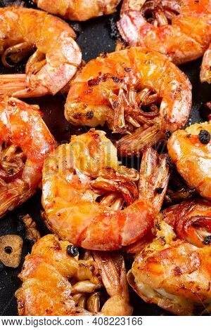 Grilled Headless Langoustines With Chunks Of Garlic, Vertical Photo