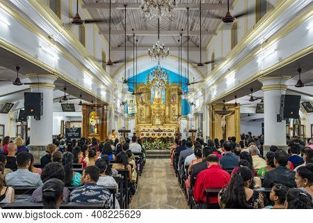 Goa, India - December 24, 2019: Unidentified indian people praying during Christmas eve mass in christian church in Goa, India