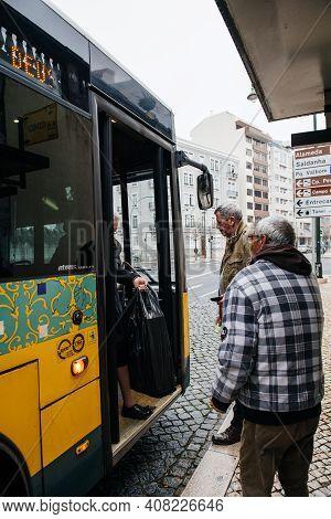 Lisbon, Portugal - Feb 9, 2018: Senior Men Waiting To Enter Yellow Public Transportation Bus At Cent