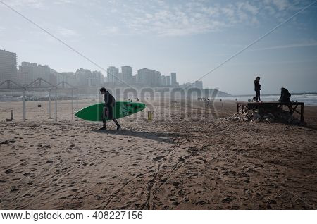 Mar Del Plata, Argentina - July, 2020: Man Surfer Carrying Surf Board On The Beach After Surfing In