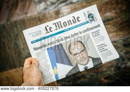 London, United Kingdom - Feb 2, 2021: Pov Male Hand Holding Reading French Le Monde Newspaper With J