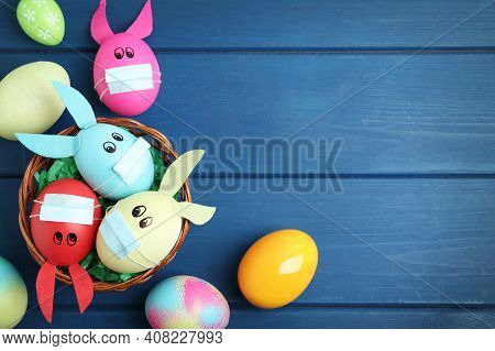 Painted Eggs Decorated With Bunny Ears, Protective Masks And Space For Text On Blue Wooden Table, Fl