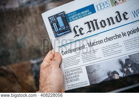 London, United Kingdom - Feb 2, 2021: Pov Male Hand Holding Reading French Le Monde Newspaper With L