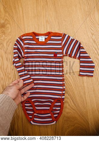 Paris, France - Feb 14, 2021: Male Hand Holding New Baby Body Manufactured By Swedish Company Polarn