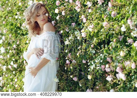 Smiling Pregnant Woman Resting In The Rose Garden. Posing Outdoors. Motherhood. High Quality Photo.