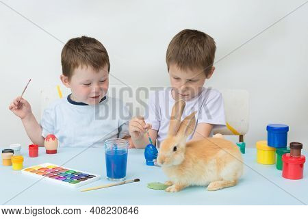 Children Paint Easter Eggs. The Boys Sit At A Table With Paints Spread Out. On The Table Is A Live E