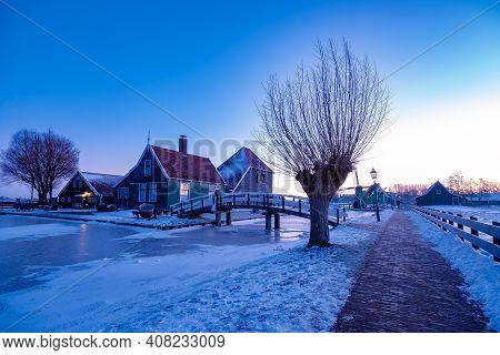 Snow Covered Windmill Village In The Zaanse Schans Netherlands, Historical Wooden Windmills In Winte
