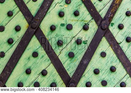 Green Wooden Background With Metal Rivets. Detail Of Old Wooden Gates, Doors With Cracked Paint. Bla