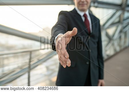 Hand of mature businessman in formalwear welcoming foreign partner while making business deal after negotiating and signing new contract