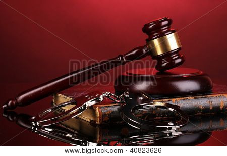 Gavel, handcuffs and book on law on red background