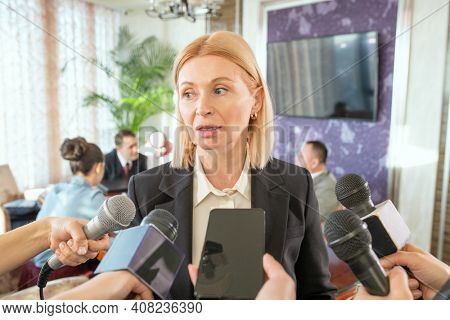 Mature blond female delegate in formalwear standing in front of journalists with microphones and answering their questions during interview