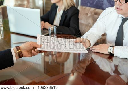 Hand of mature male delegate passing document with financial data to business partner against secretary sitting by table in front of laptop