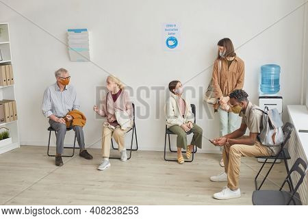 Wide Angle View At Hospital Waiting Room With Diverse Group Of People Waiting In Line For Vaccinatio