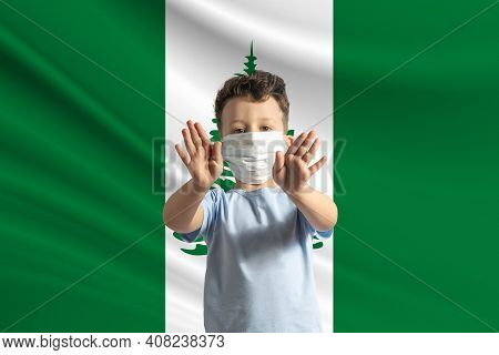 Little White Boy In A Protective Mask On The Background Of The Flag Of Norfolk Island. Makes A Stop