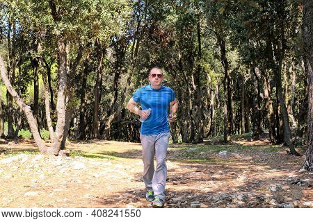 Running Man Jogging For Fitness Running In Beautiful Landscape Nature Outdoors. Handsome Young Spotr