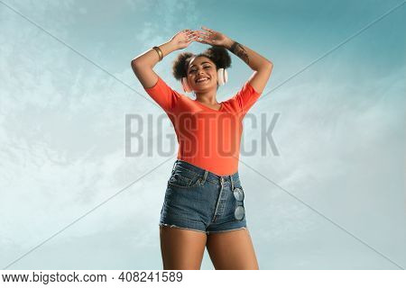 Music. Portrait Of Young Female Fashion Model On Blue Sky Background. Beautiful African Woman With T