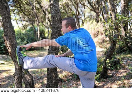 Handsome Muscular Young Man Is Doing Stretching Exercises In Forest. Sportsman Wearing Sportswear In