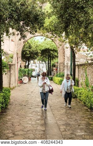 Campania, Italy - June 28, 2014: Tourists Exploring The Streets Of Campania On A Rainy Summer Day In