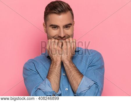 portrait of excited casual man in denim shirt holding finger to mouth and enthusiastically waiting and smiling on pink background in studio
