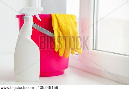 A Pink Plastic Bucket And Yellow Gloves On A White Windowsill. Preparation For Cleaning And Washing