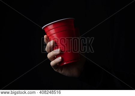 Red Plastic Cup With A Hand In The Dark, Close Up.