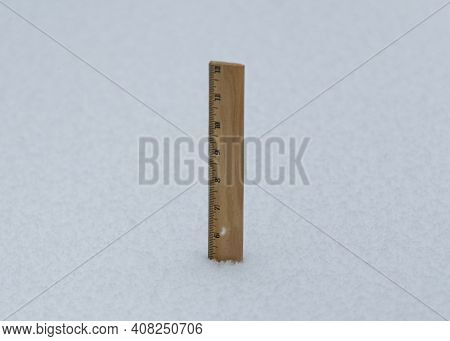 A Wooden Ruler Sticking Out Of Fresh Snow Fall Showing That 5 Inches Has Fallen So Far During A Bliz