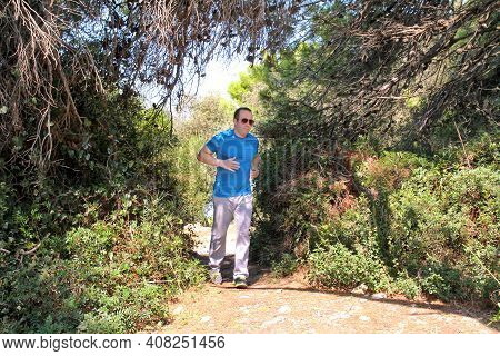 Fit Runner Man Jogging For Fitness Running At Running Trail In Beautiful Landscape Nature Outdoors.