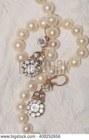 Close Up Of White Pearl Necklace On An Ivory Fabric With Vintage Gold Earrings - Regency Fashion Ins