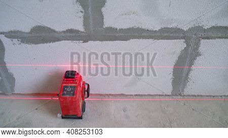 A Builder Makes Arrangements With A Laser Level At A Construction Site. Construction Laser Level And