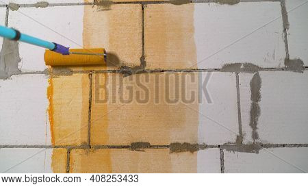 The Orange Wall Is Covered With Red Paint. Roller And Orange Wall. Paint Roller With Orange Paint. A