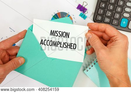 The Businessman Takes Out A Card From The Envelope With The Text Mission Accomplished, On The Backgr