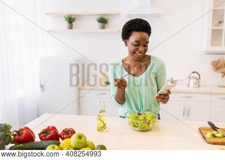 Weight Loss App. Black Woman Using Smartphone Eating Healthy Vegetable Salad Enjoying Dinner In Mode