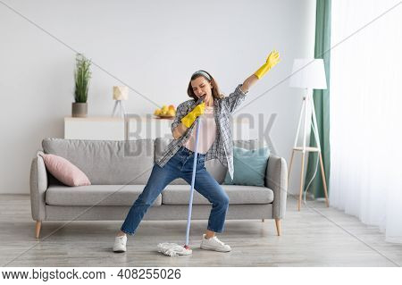 Happy Young Woman Cleaning Her Home, Singing At Mop Like At Microphone And Having Fun, Free Space. M
