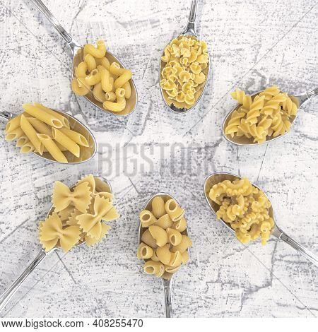 Various Pasta On Spoons On A White Stone Background. Different Sort Pasta On Spoons Laid Out In A Ci