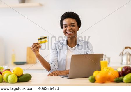 African American Woman Doing Grocery Shopping Online Showing Credit Card Sitting At Laptop Computer